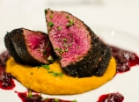 Coffee-rubbed seared elk medallions, sweet potato puree, and huckleberry demi-glace